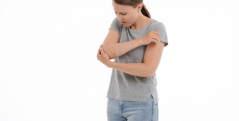 kobieta, która chwita się za łokieć z miną wyrażającą ból