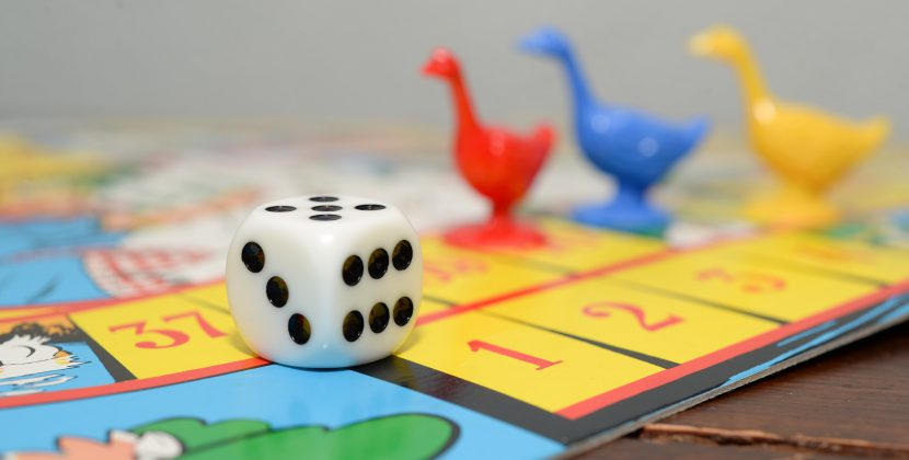 rozłożona gra planszowa, widać planszę, pionki w kształcie gąsek i kostkę do gry
