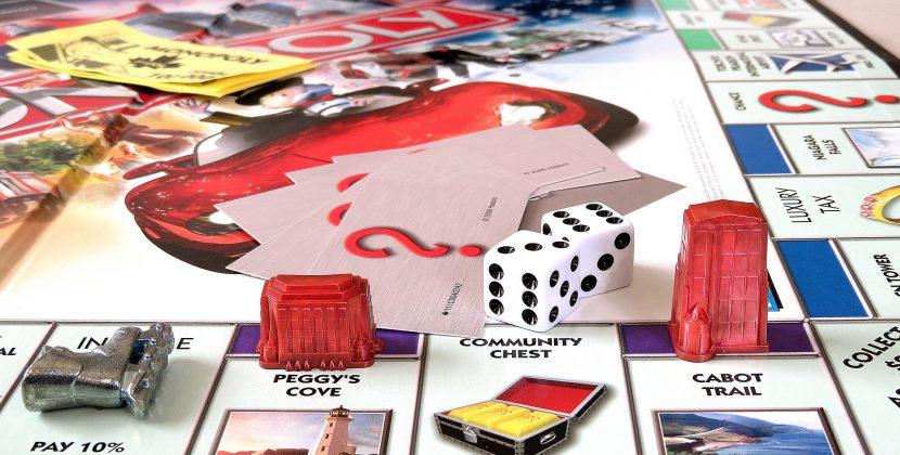 Rozłożona gra planszowa, na planszy plastikowe elementy, kości do rzucania i karty