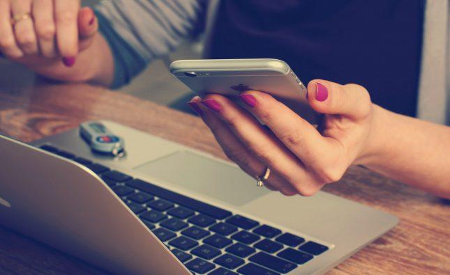 laptop uzyskany poprzez wypożyczenie laptopa; na obrazku laptop i telefon, który trzyma kobieta